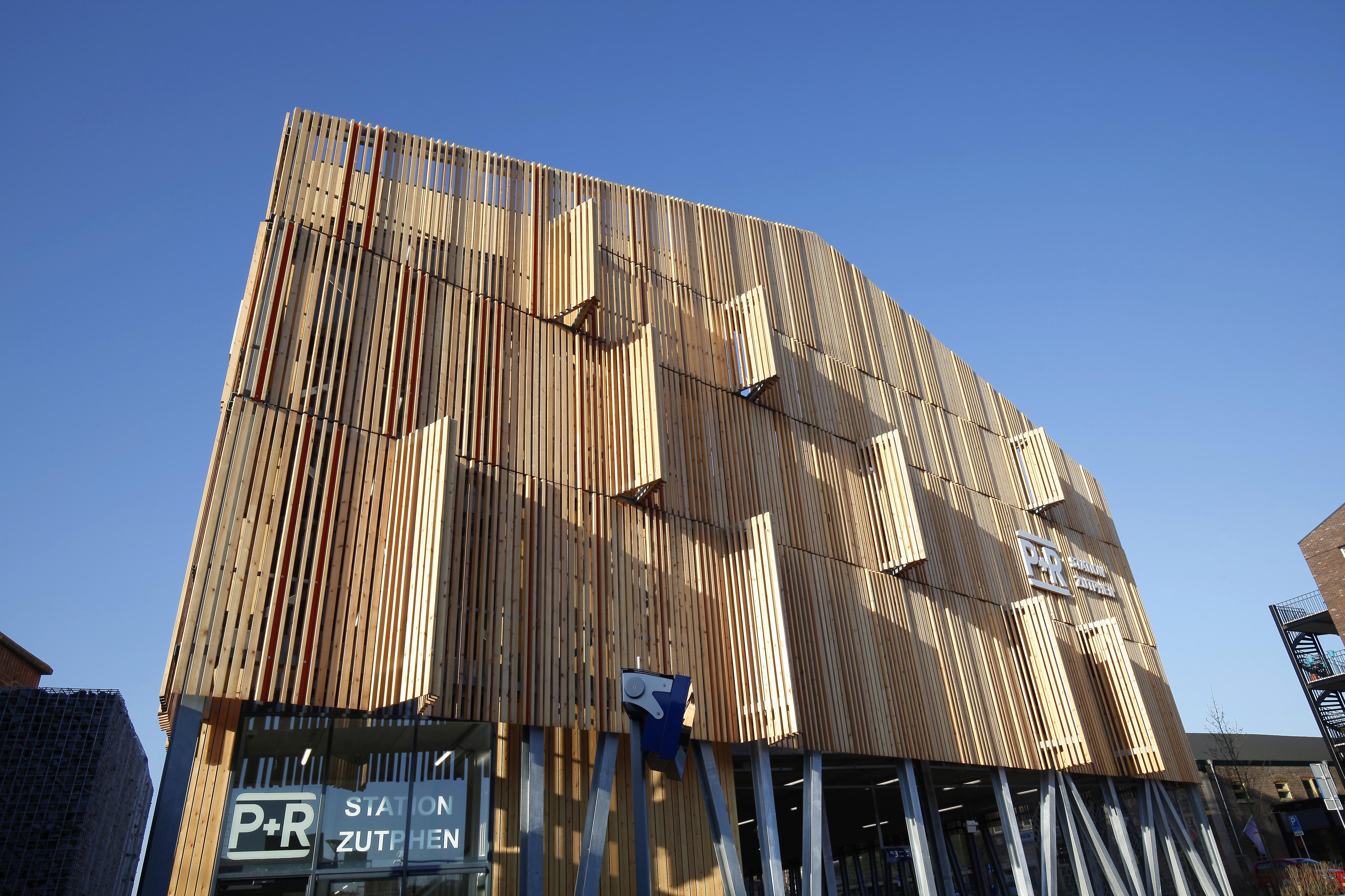<p>Ledverlichting en contrasterende oranje strips die half verscholen gaan achter de houten lamellen en de uitkragingen boven de voetgangersentree geven het gebouw een zekere dynamiek. Foto: Harry Noback</p>