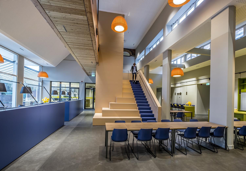 <p>Werkcafé met centrale trap/loopbrug/lift als hart van de organisatie. Foto: Hans de Rooy</p>