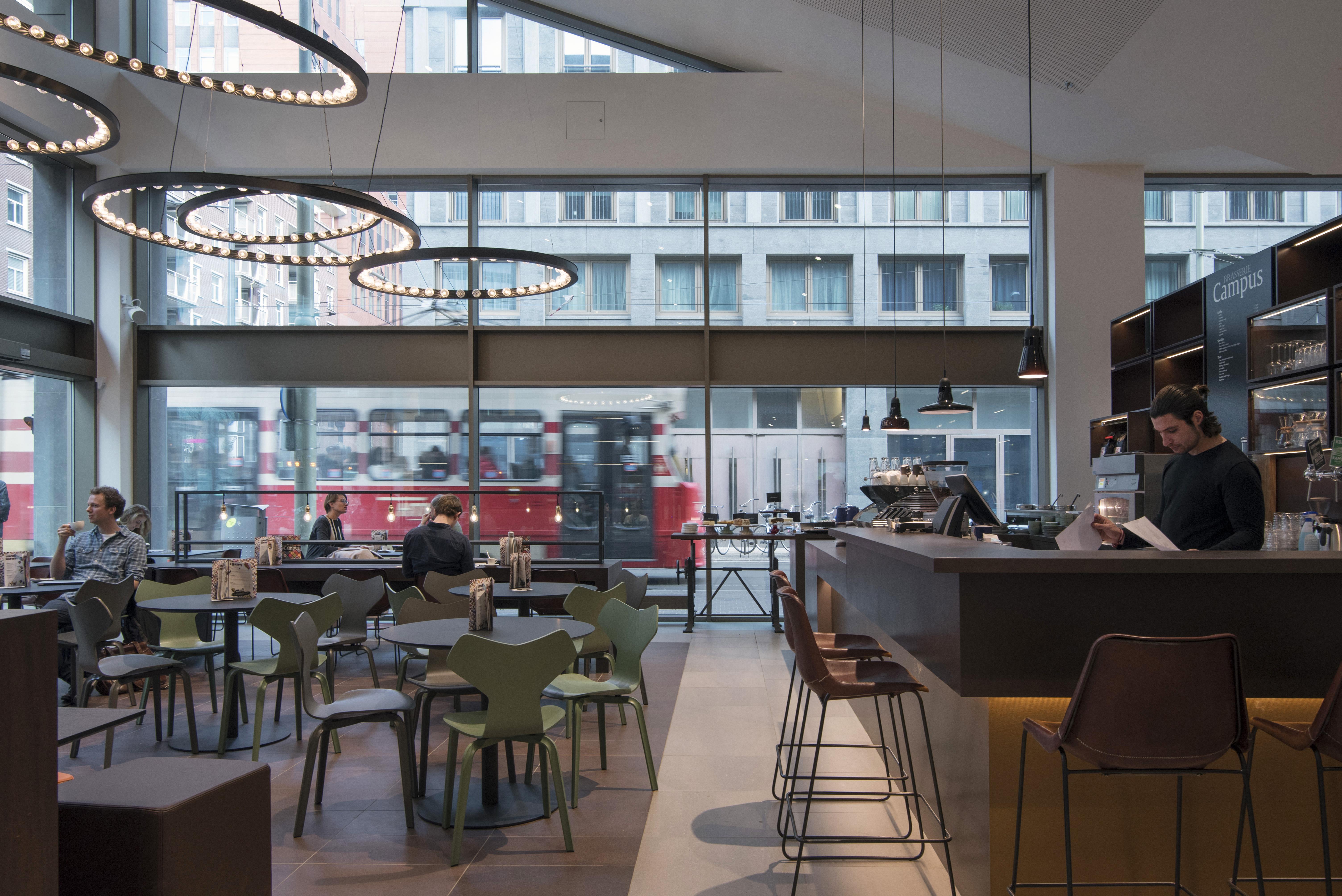 <p>De koffiebar naast de entree zorgt voor een publiek en levendig karakter. Fotografie: Peter de Ruig</p>