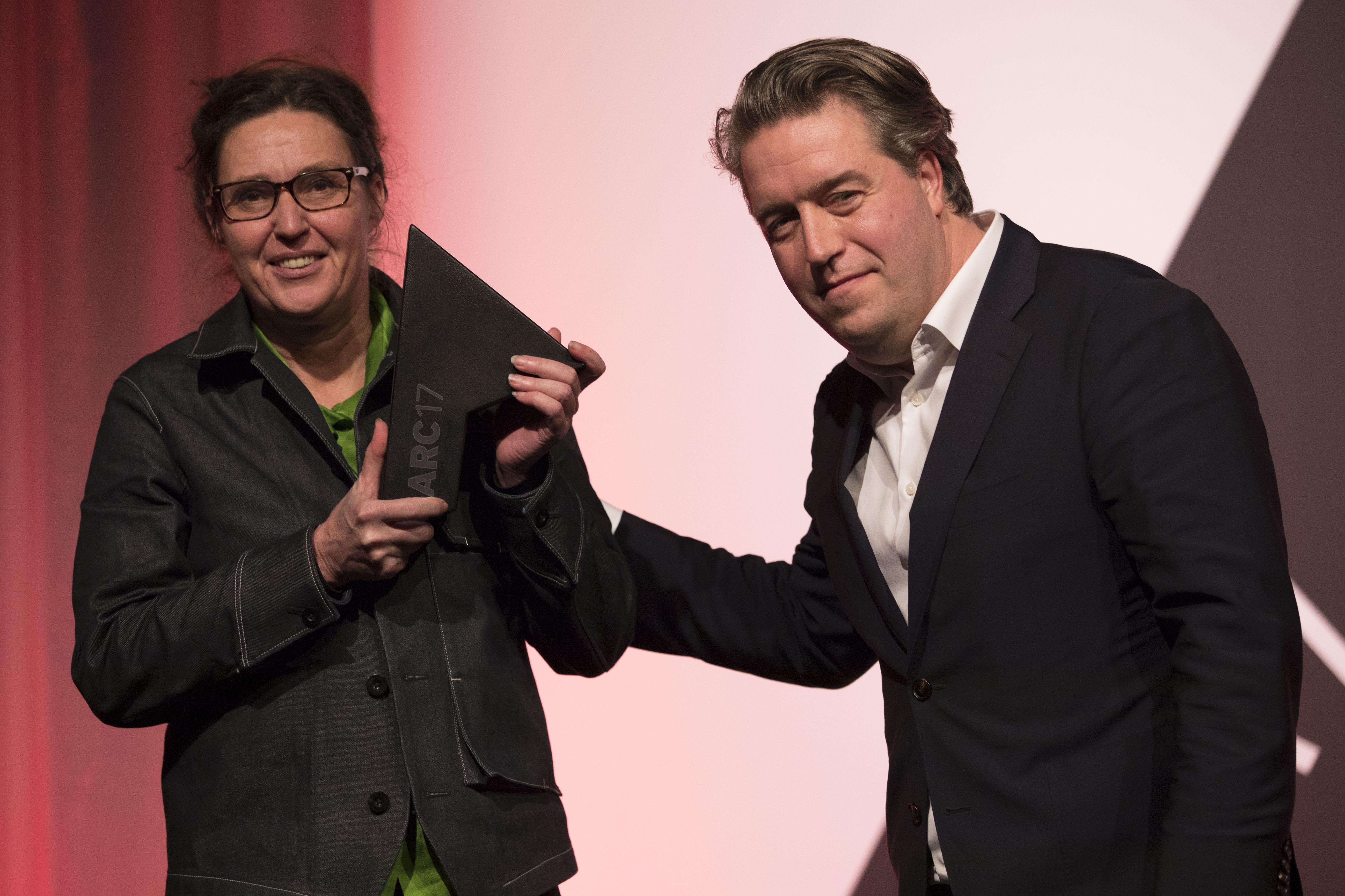<p>Ellen van Loon OMA ontvangt uit handen van Nanne de Ru (juryvoorzitter ARC17 Architectuur Award) de prijs voor Rijnstraat 8 in Den Haag. Foto Elvins Fotografie</p>