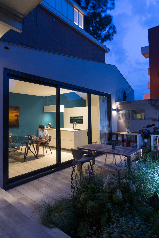 <p>Van de keuken in de moderne uitbouw loop je zo door de opstaande pui de tuin in. Door deze grote opening wordt de tuin een extensie van de leefruimte.</p>