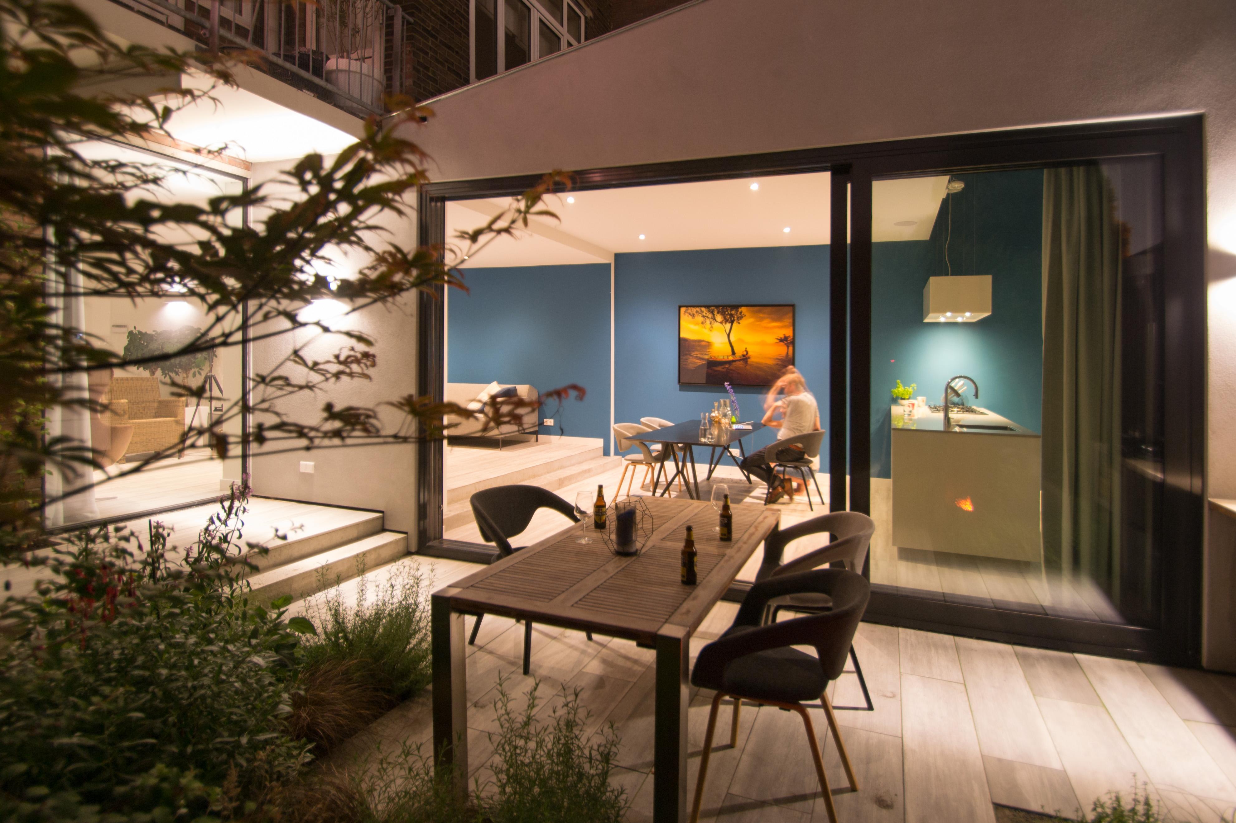 <p>De binnen en buiten ruimten vloeien in elkaar over. Zowel in de moderne uitbouw als in de tuin liggen twee tredes, waardoor de verbinding tussen binnen en buiten wordt versterkt.</p>