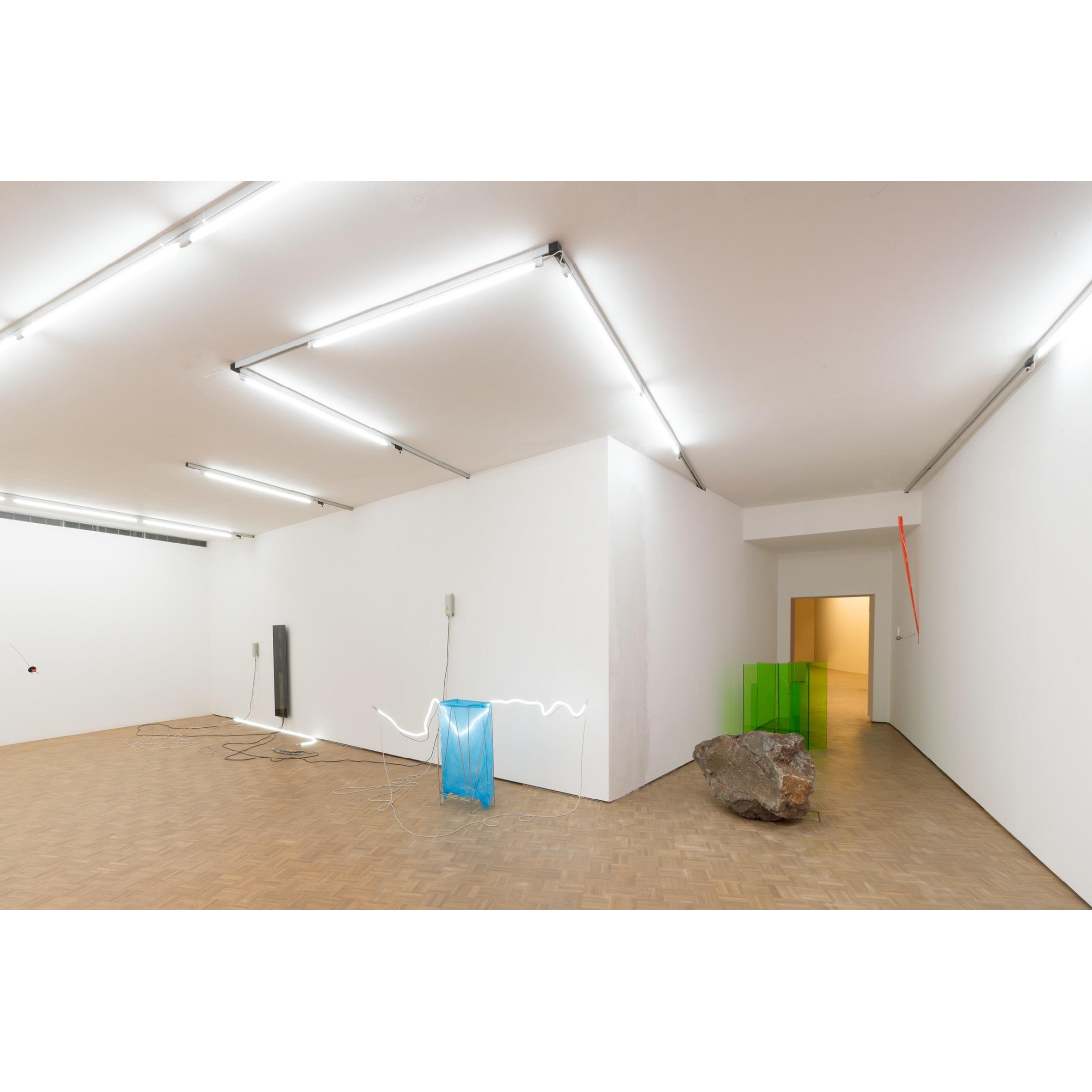 <p>De installatie van Noor van Imhoff begint in de paars verlichte personenlift die sterk contrasteert met de felgroene expositiezaal Beeld Sanne van Hecke</p>