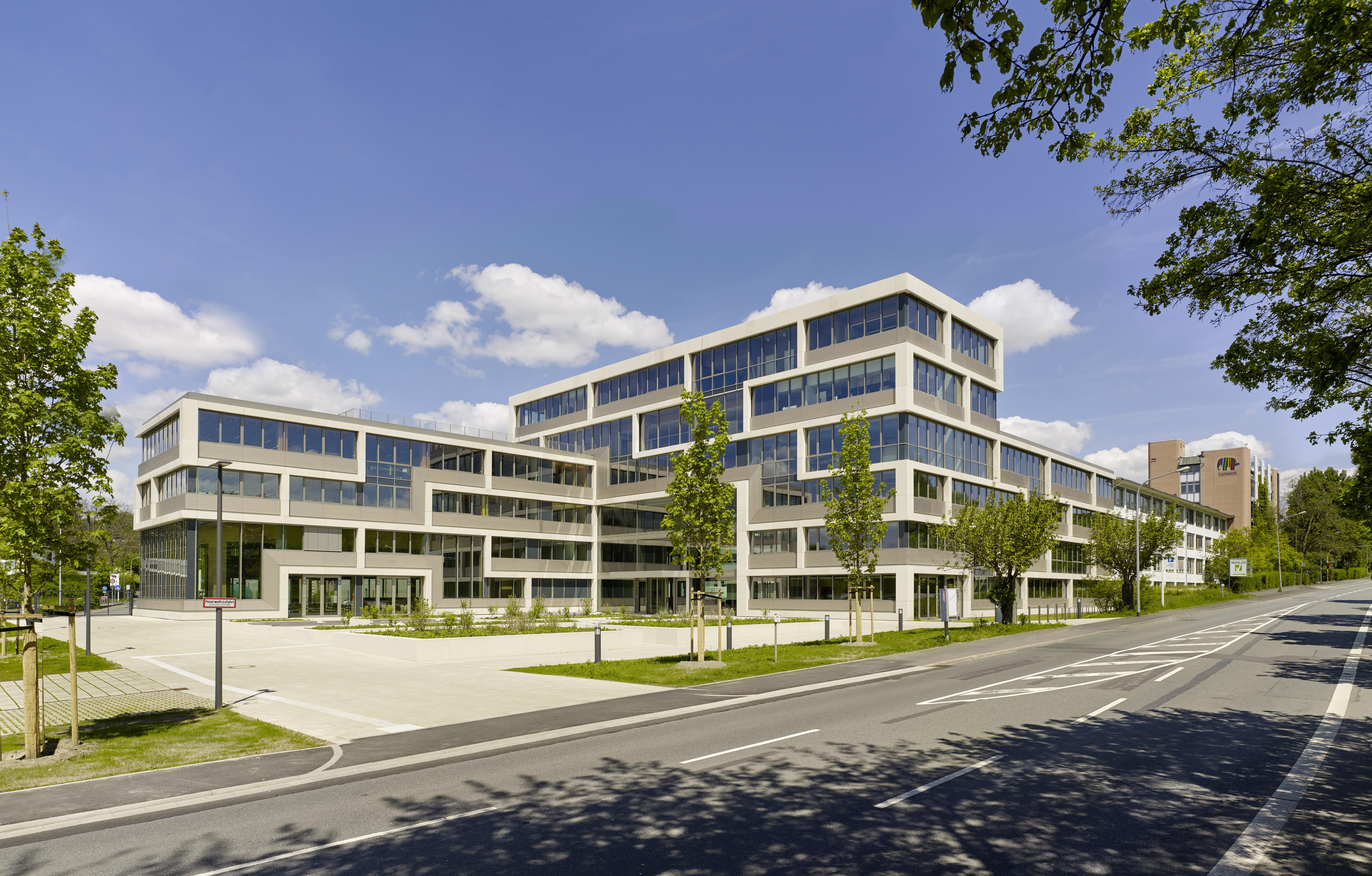 <p>Het hoofdkantoor van DAW gezien vanaf de straat. Alle verdere gebouwen aan deze straat worden door Brückner & Brückner getransformeerd. Beeld Constantin Meyer </p>