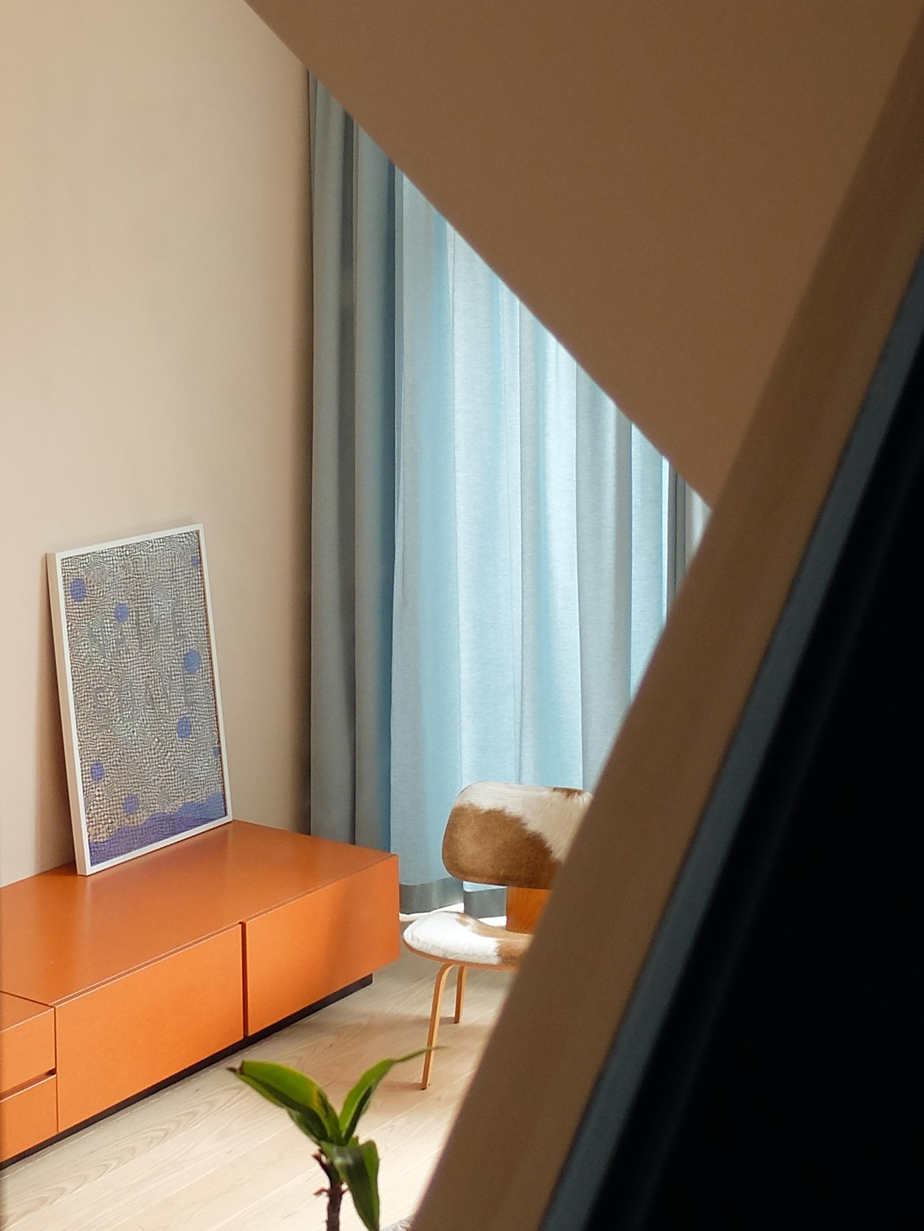 <p>Driehoekige ramen bieden een glimp van de woonkamer gezien vanaf de trap</p>
