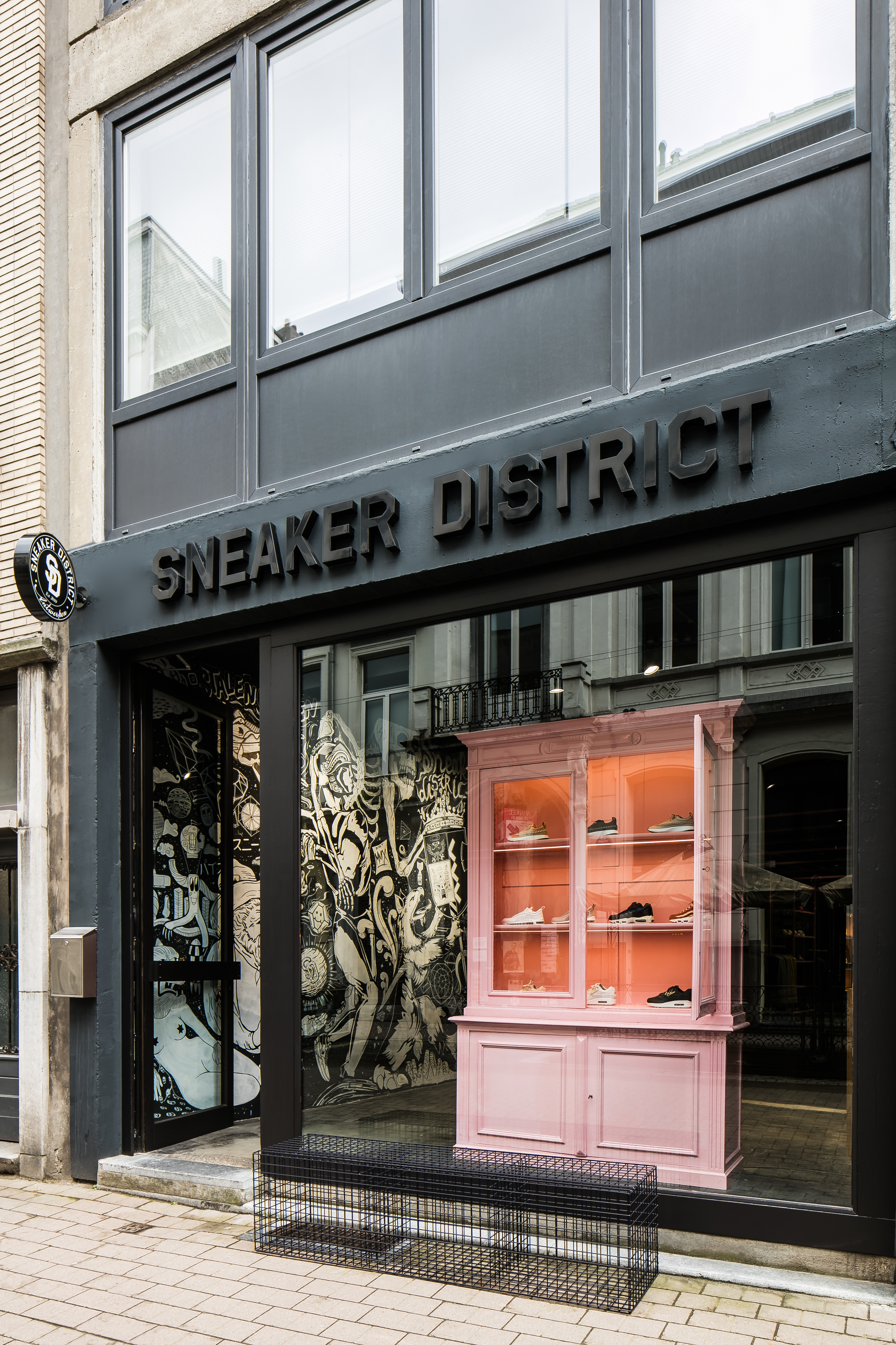<p>Dark grey facade of the store with the pink antique cabinet referencing to the Kloosterstraat antique- store heritage.</p>