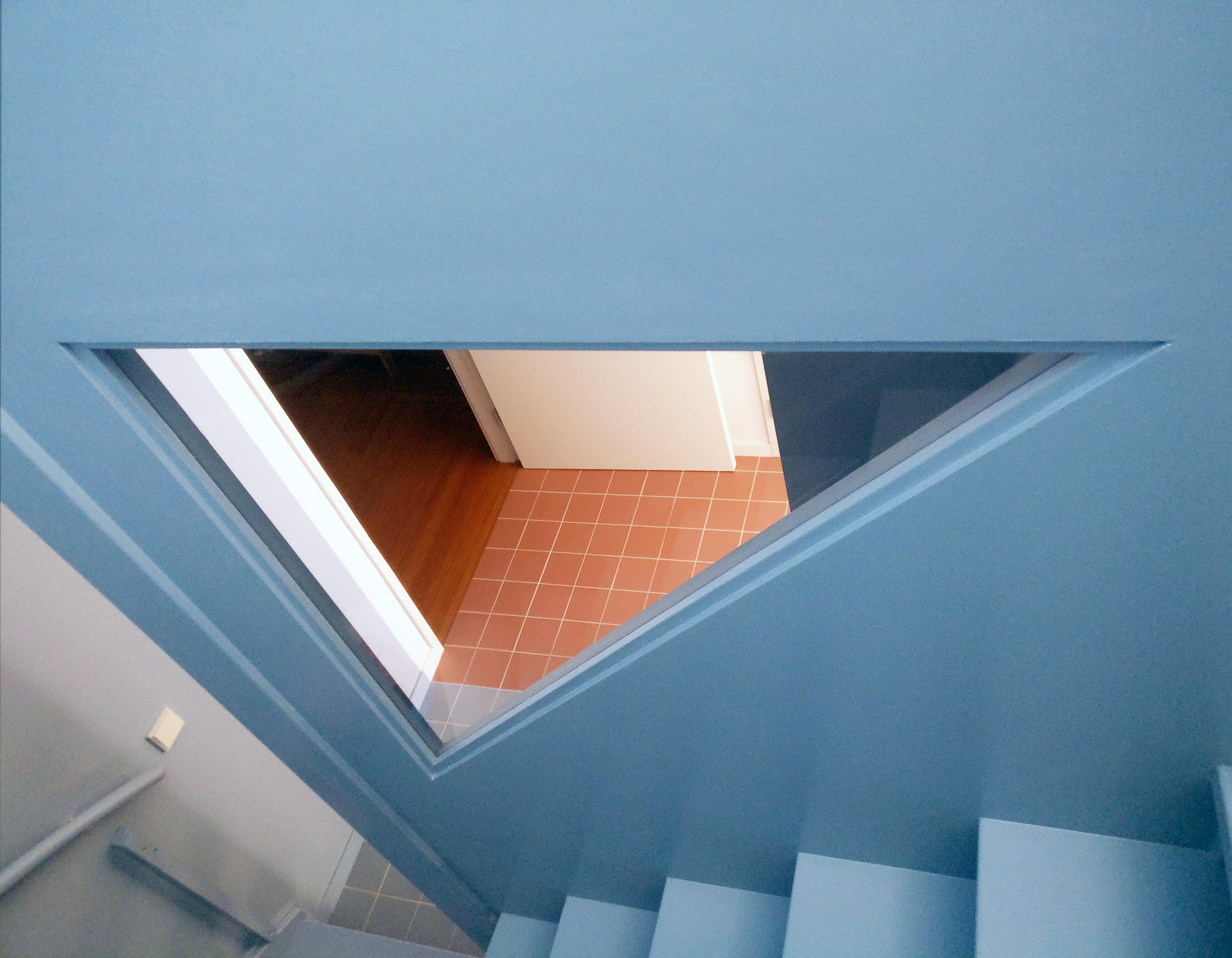 <p>Zicht door een van de driehoekige ramen in het trappenhuis op de overloop, het hart van het huis.</p>