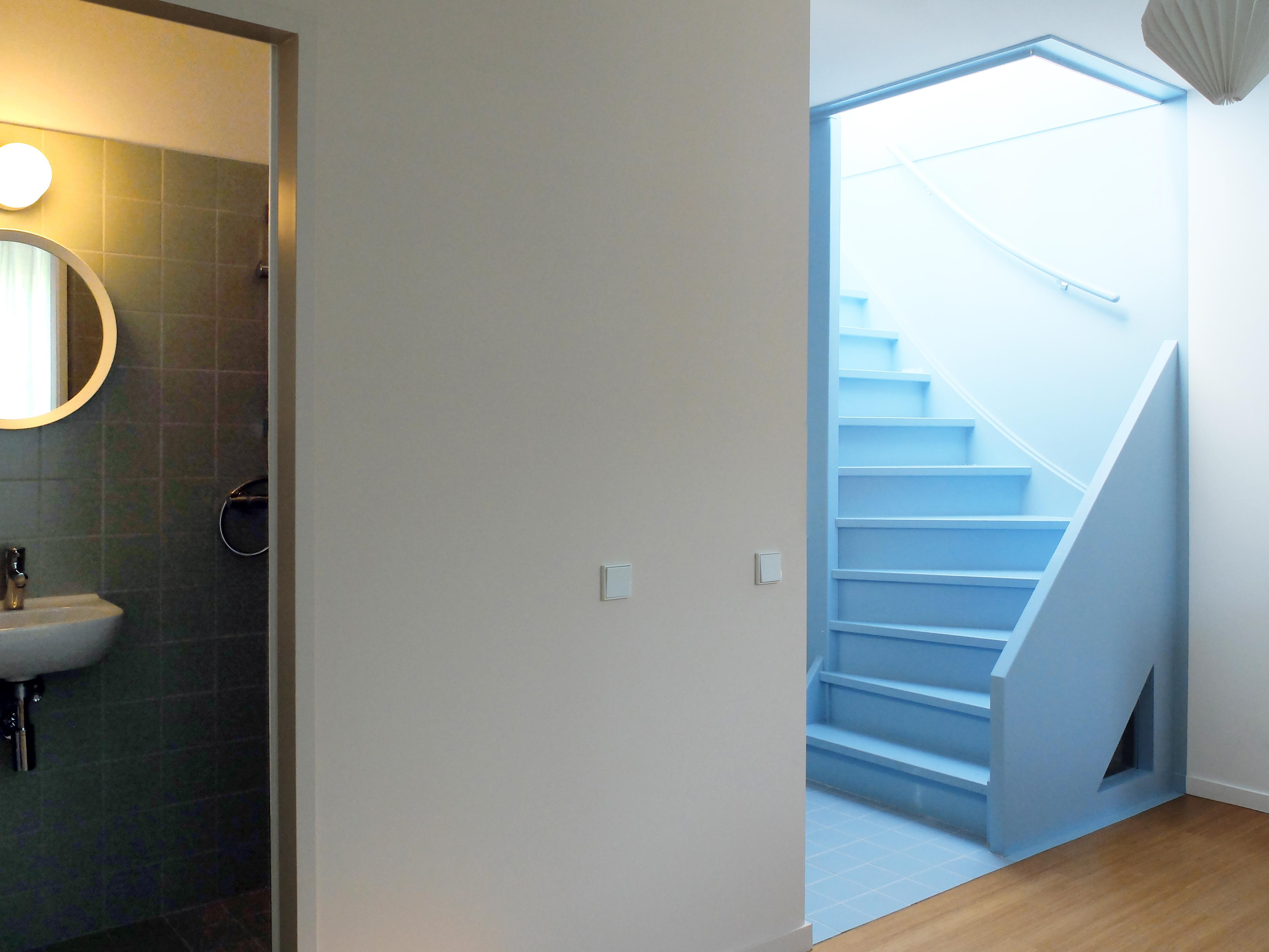 <p>De trap naar het dakterras. Via het driehoekige raampje valt er daglicht in de ondergelegen trap</p>