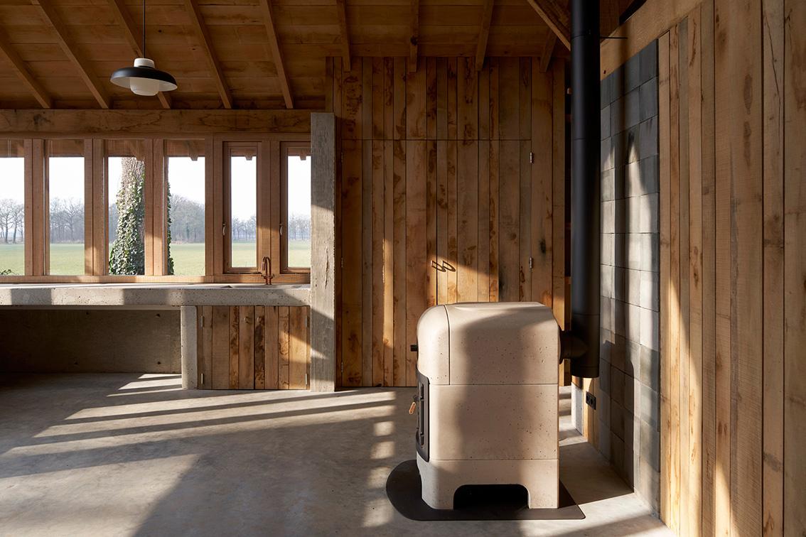 <p>een betonnen houtkachel verwarmt de werkplaats c.q. vergaderruimte – foto Rene de Wit</p>