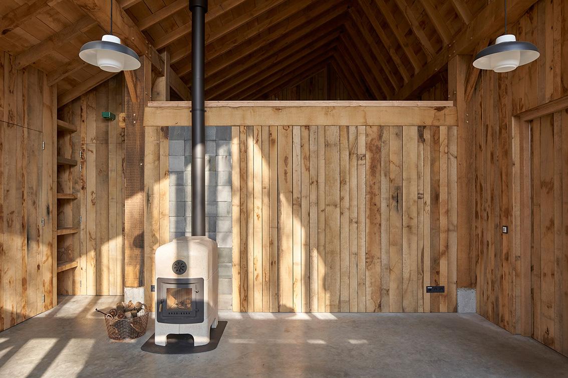 <p>achter de wand met de kachel bevindt zich de trap naar de verdieping, het eikenhouten interieur geeft een totaalbeleving van de onvolmaaktheid van het eiken – foto Rene de Wit</p>