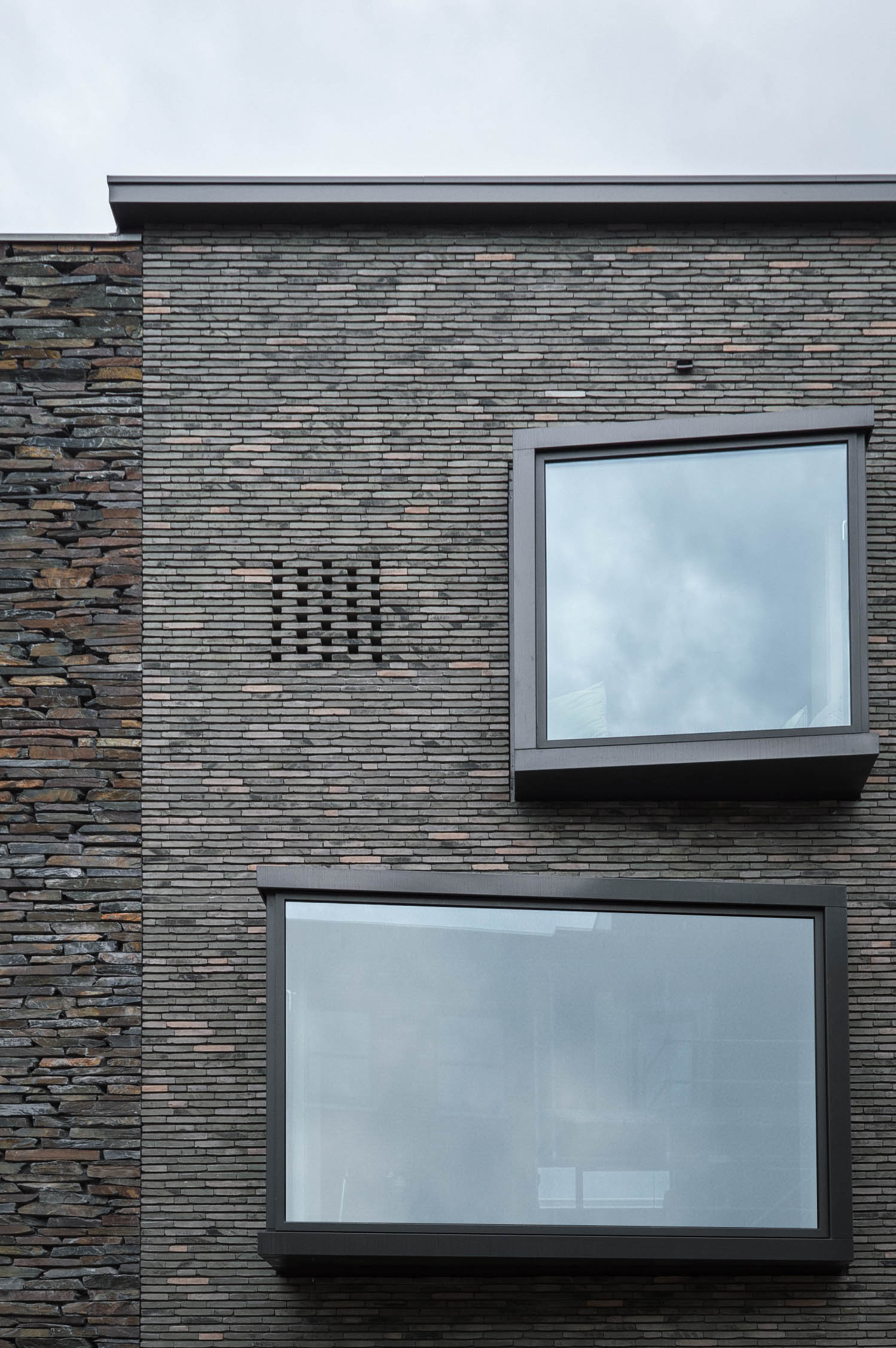 <p>Met de strakke en gladde vormgeving staan de erkers in contrast met het grillige, gesloten gevelvlak</p>