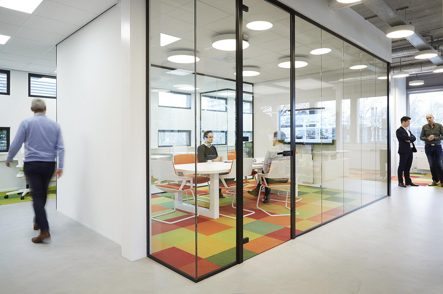 een transparante vergaderruimte zorgt voor scheiding tussen dynamiek en rust