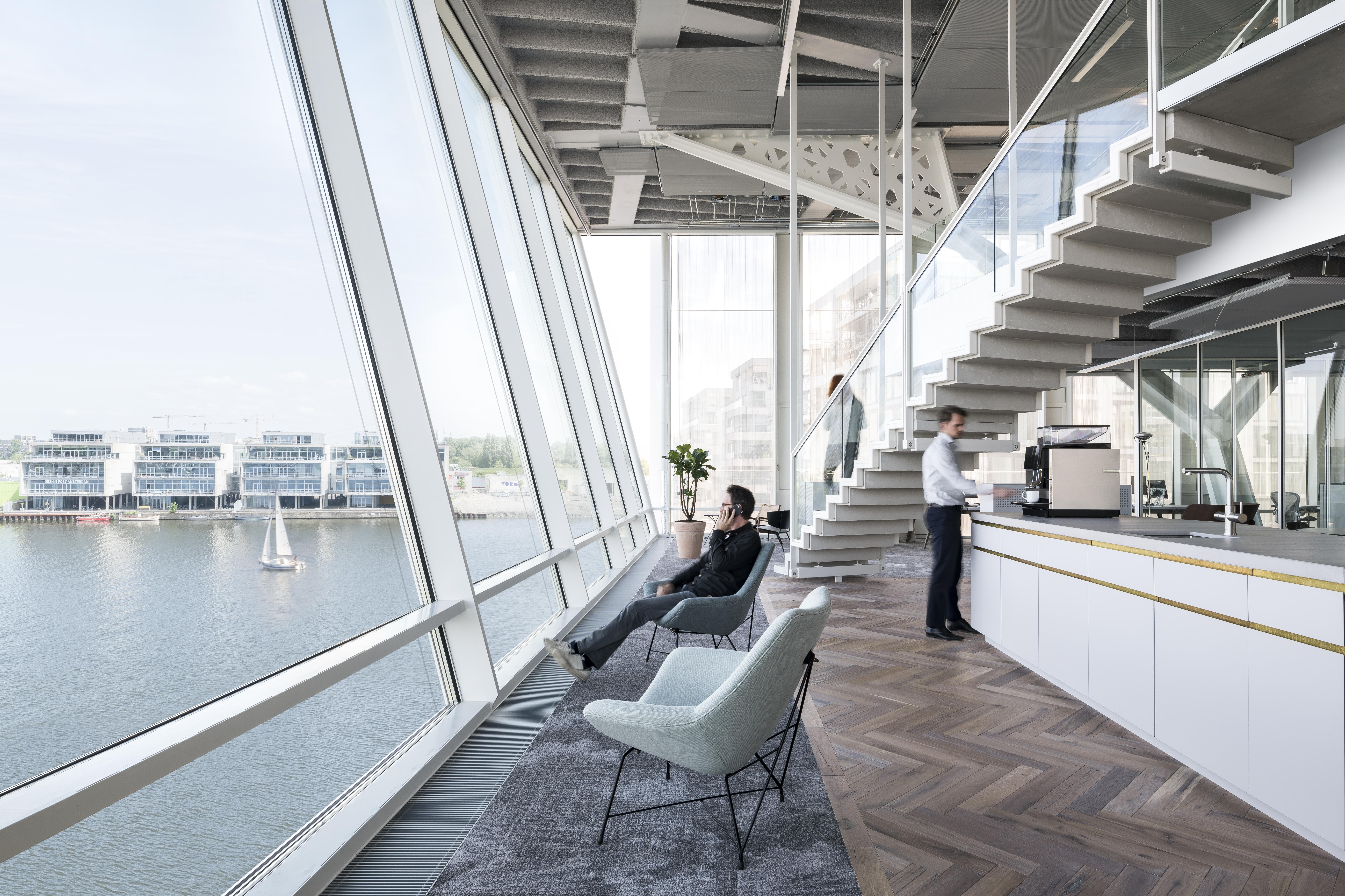 <p>Uitzicht op de entrepothaven vanuit twee vintage Borsani stoelen. Beeld: Studio de Nooyer</p>