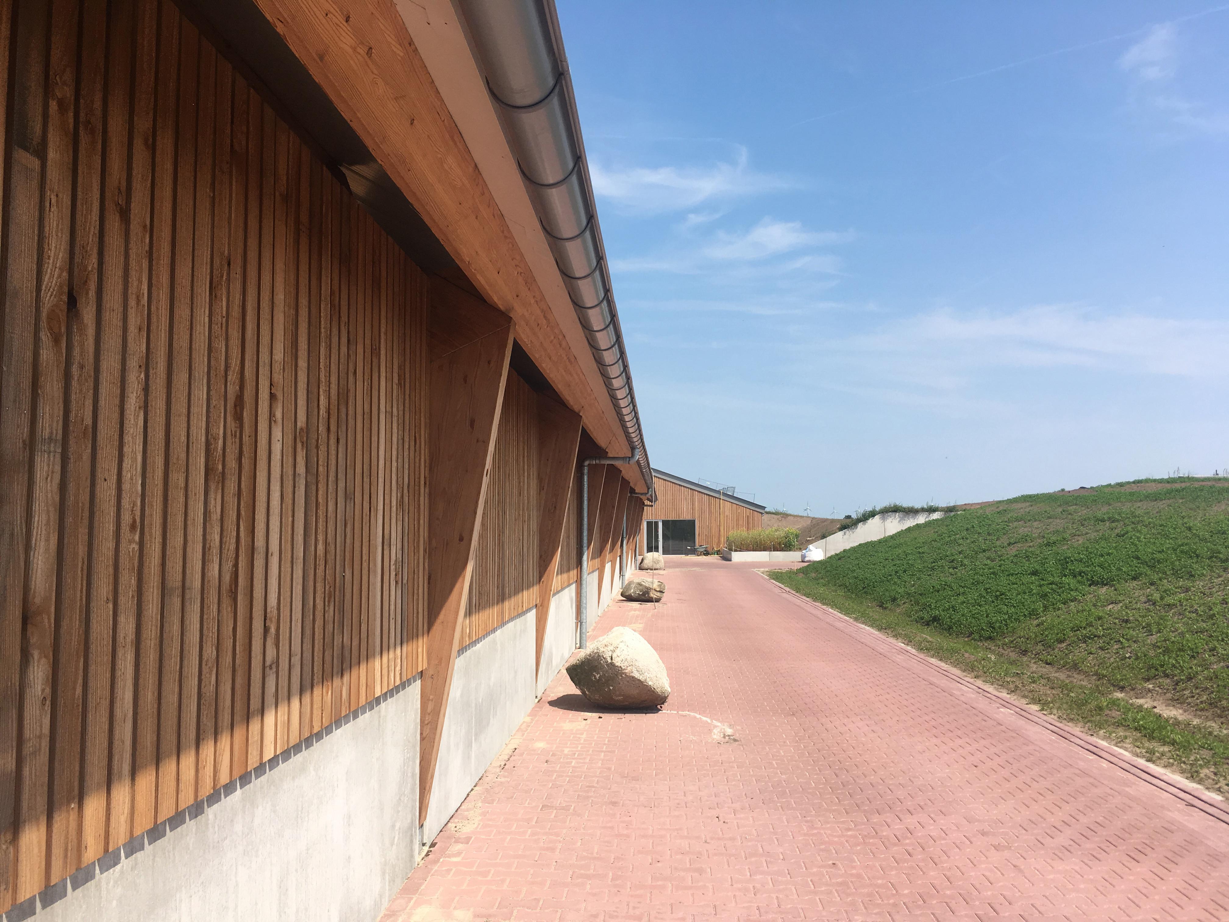 <p>De oprit naar het boerenerf. Op de plek van de glooiende heuvels was in eerste instantie een betonnen wand bedacht, maar DAAD zag hiervan af en gat het terrein een opener uitstraling. Beeld Walter Frisart FOTOwerk</p>