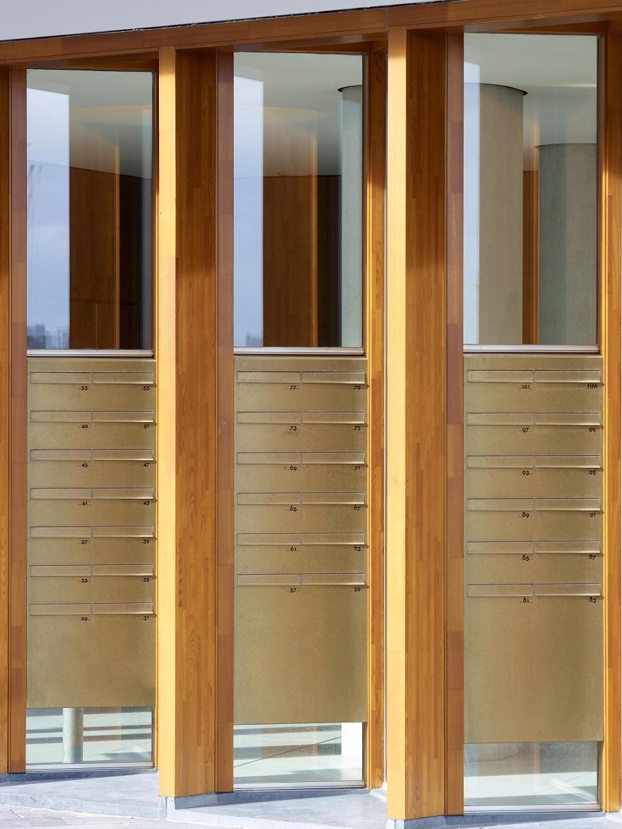 <p>Messing brievenbusen en een houten afwerking geven de entrees een warme uitstraling. Beeld Jeroen Musch</p>