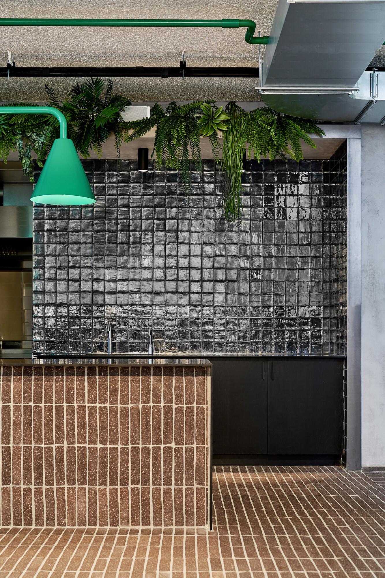<p>Groen van kabelboom en planten en grafisch zwart ontmoeten elkaar in de open keuken van het restaurant. Hier bedienen de werknemers zichzelf, zodat alle ruimtes vrij toegankelijk en laagdrempelig zijn. fotografie Philip Jintes @ Phenster</p>