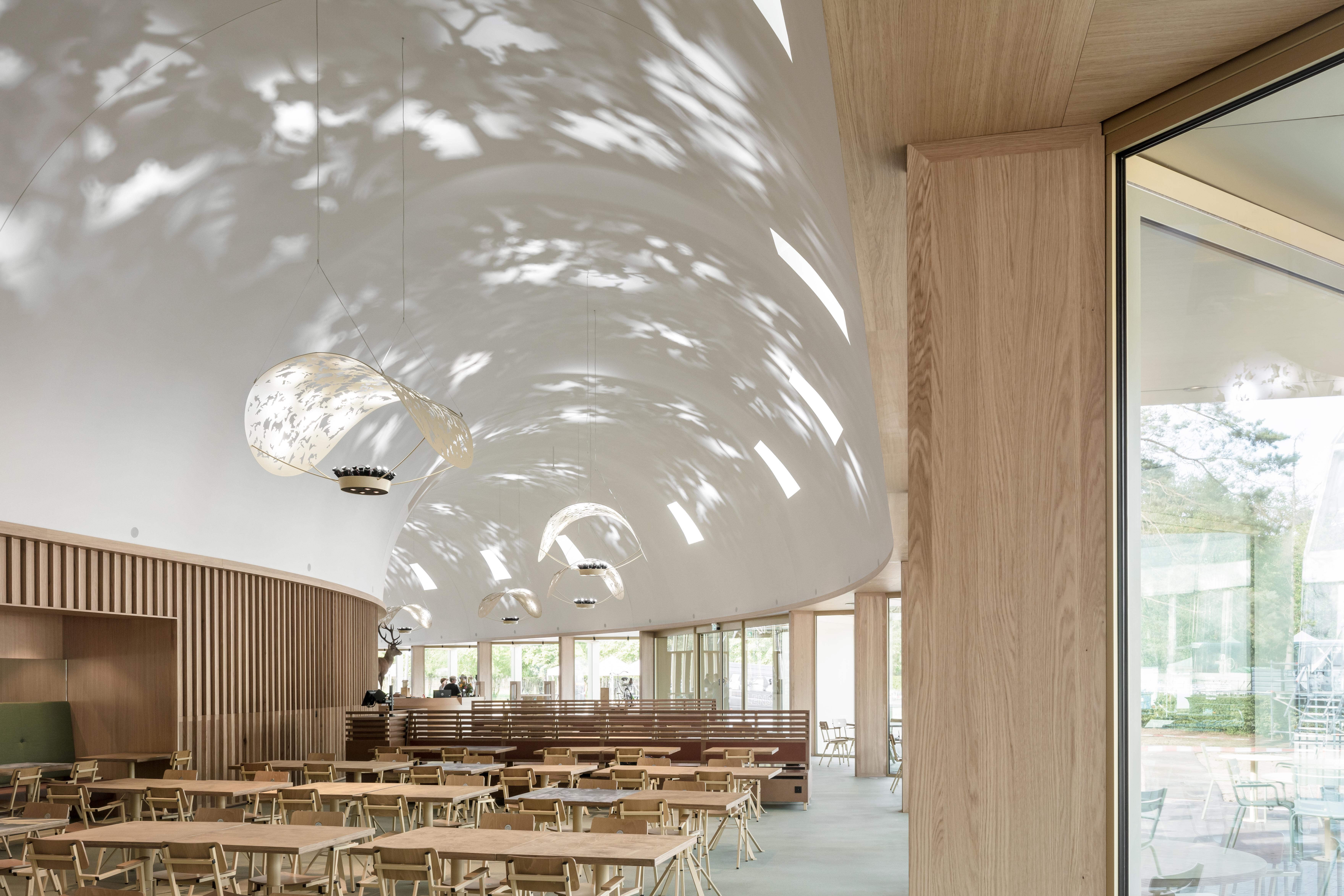 <p>Het restaurant is ondergebracht in een hoge gebogen ruimte onder een hoog wit gepleisterd gebogen dak. Deze ruimte strekt zich uit over de lengte en huisvest ook de balie en de winkel.</p>